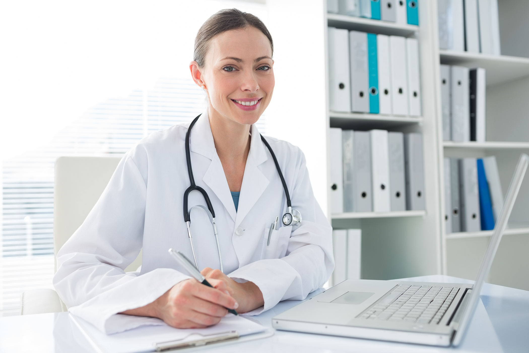 Beautiful female doctor with laptop and clipboard sitting at des